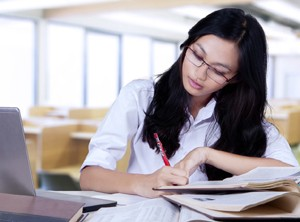 A distance learning student working from books and a laptop