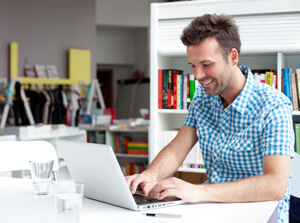 A male distance learning student studying from a laptop