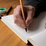 Man writing in blank book