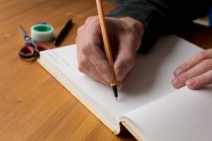 Man writing in blank book