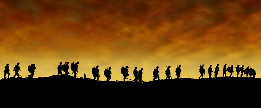 Soldiers walking in a line with sun setting in the background