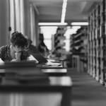 Black and white photo of woman studying in library