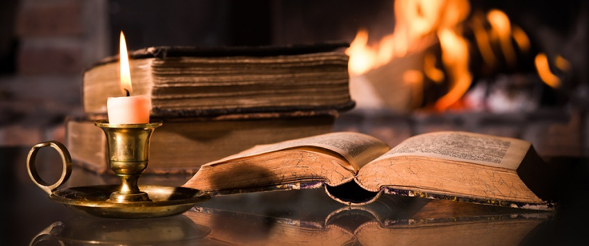 Open book next to a candle and log fire