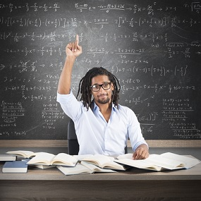Student studying Mathematics A level in front of a board covered in formulas